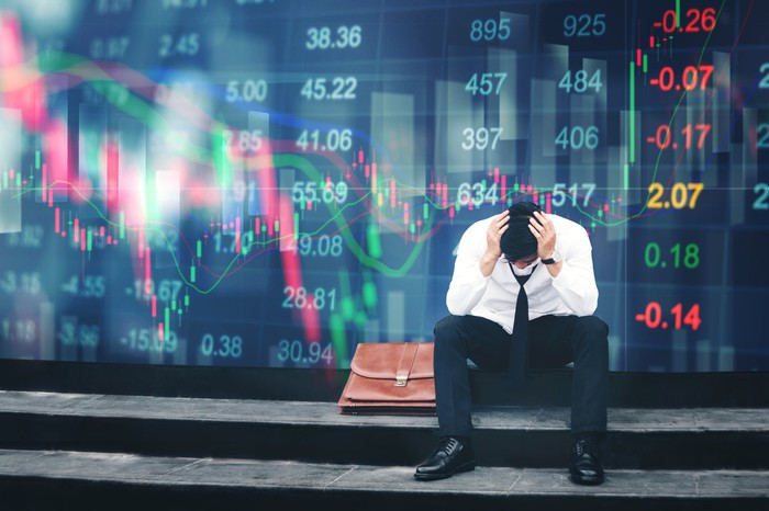 A man in a suit, with a briefcase next to him, sits with his head in his hands in front of a wall of stock tickers.