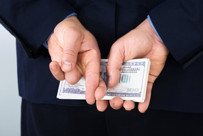 A businessman in a suit holding a neat stack of cash behind his back while also crossing his fingers.