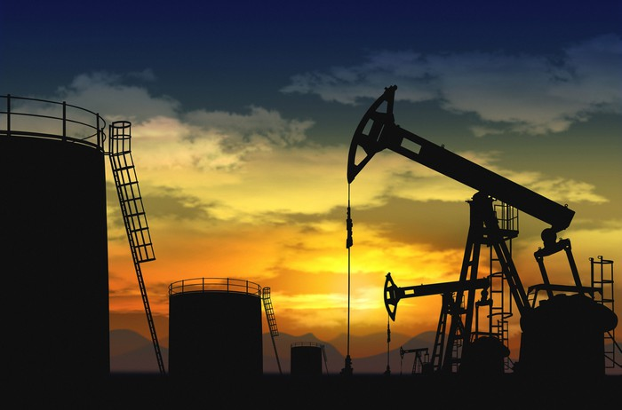 Oil pumps and storage tanks with the sun setting in the background.