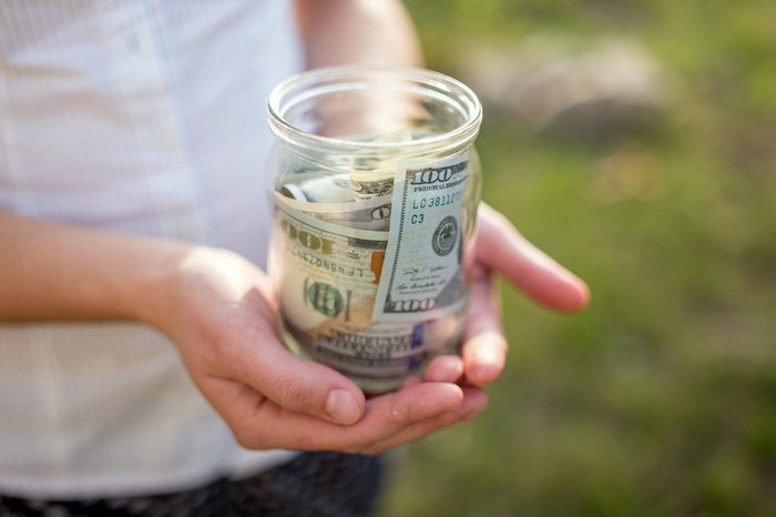 Woman holding jar filled with $100 bills
