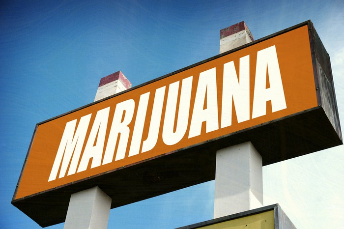 A large sign in white block lettering that reads, Marijuana, outside of a dispensary.