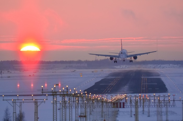A plane landing during sunset.