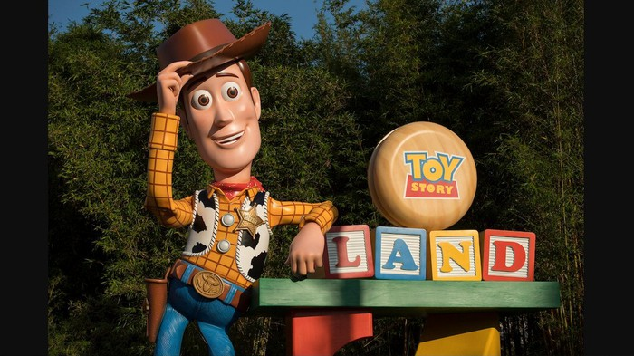 Woody figure in front of the Toy Story Land entrance at Disney's Hollywood Studios in Florida.