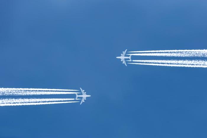 Two planes in flight seen from below.