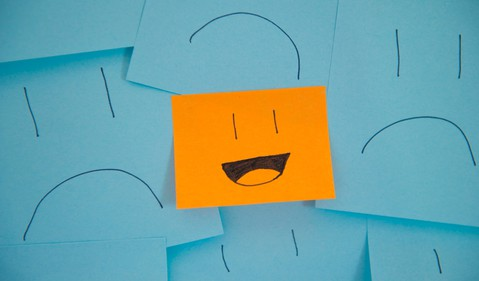 Sticky notes with sad faces and one smiley face