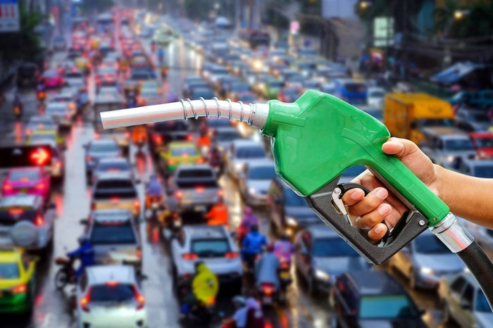A fuel pump with cars in traffic in the background.