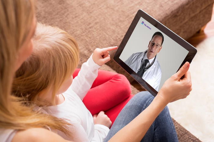 A mom and her child looking at a tablet with a Teladoc doctor on it.