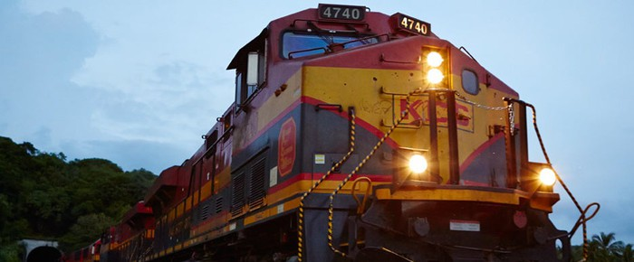 A Kansas City Southern locomotive emerging from a tunnel at dusk.