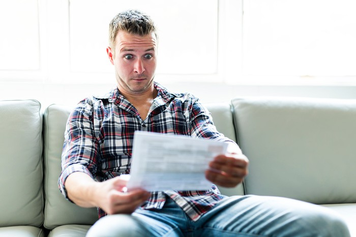 A man staring at a document with a shocked expression while sitting on a sofa.