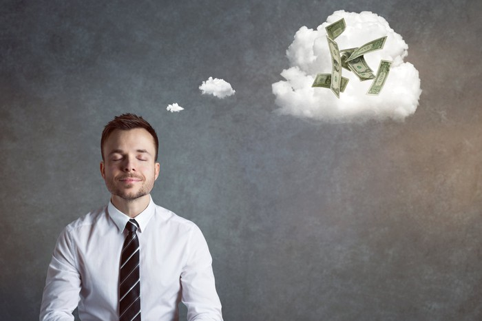 A man in a shirt and tie with a dream cloud above his head filled with money.