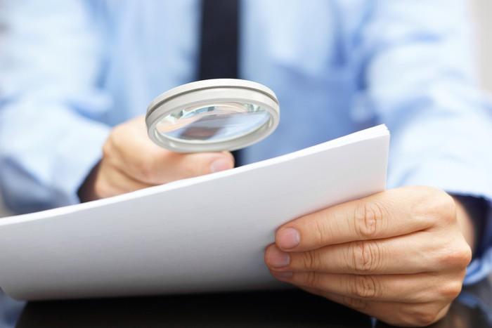 Businessman holding magnifying glass up to a document