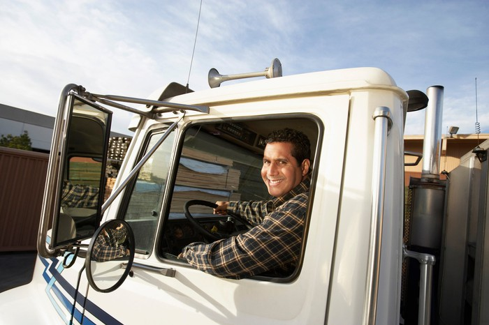 A truck driver smiles from the window of his cab.