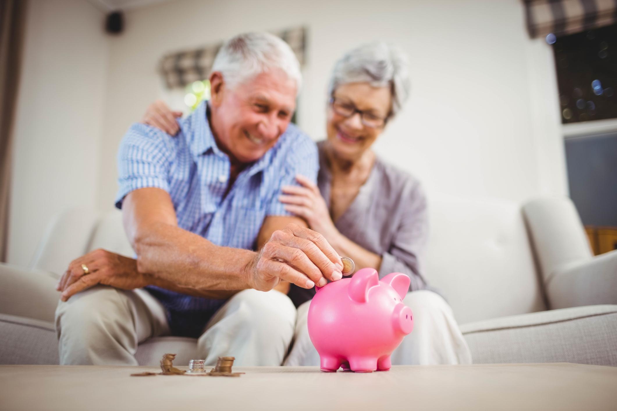An older man sitting next to an older woman puts a coin into a piggy bank