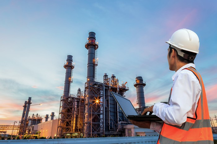 Engineer with laptop stands before an oil refinery at dusk.