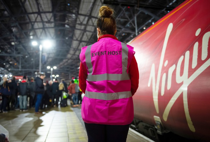 A woman stands next to a Virgin-branded train in the U.K.