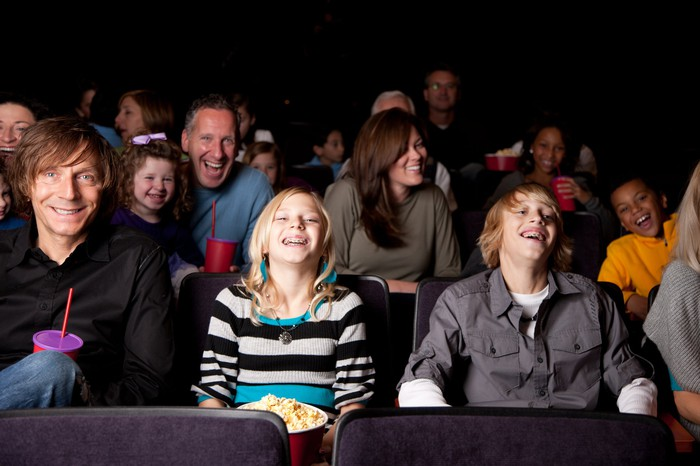 People of various ages -- some of whom are eating popcorn or drinking beverages -- sitting in seats in what appears to be a movie theater.