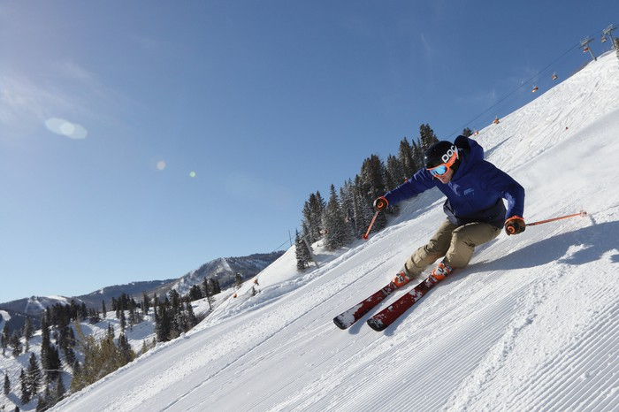A skier on his edges on a steep slope.