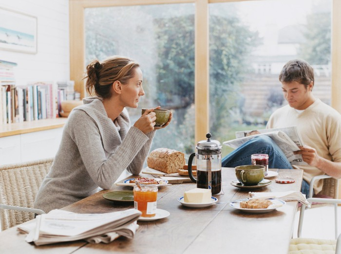 A young couple reads the daily paper at the breakfast table.