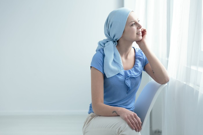 Female cancer patient staring out of a window in an all-white room