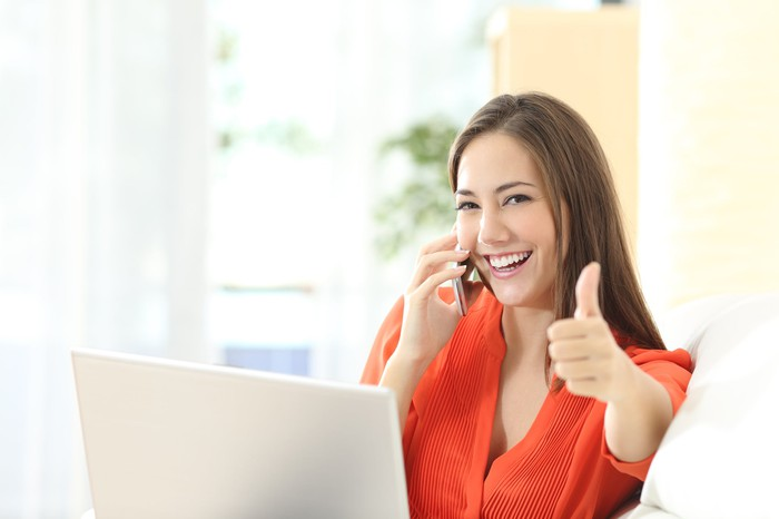 Woman talking on phone showing thumbs up