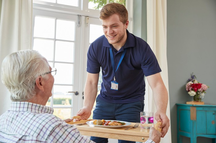 Male service provider bringing a meal to an elderly man.