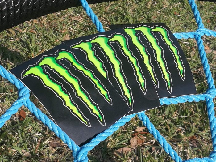 Three decals with Monster Energy logos resting on a bright blue mesh of ropes.
