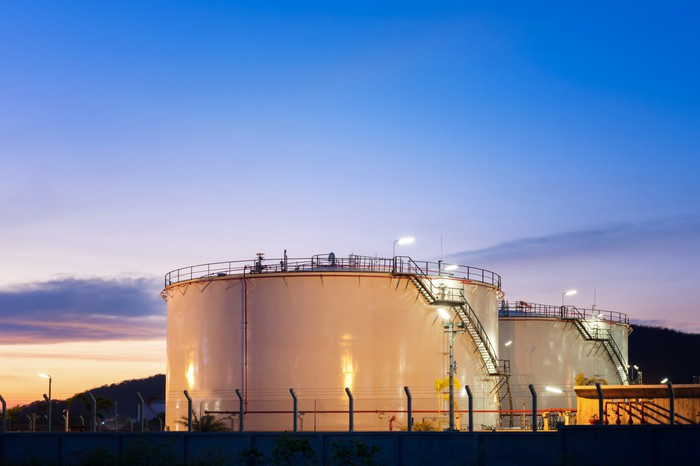 Petroleum storage tanks with the sun setting in the background.