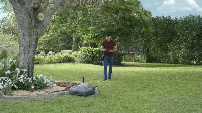 Man setting up an iRobot Terra robotic lawn mower