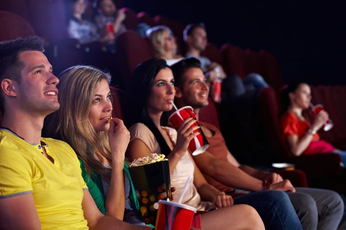 A group of people sitting in a theater, eating popcorn and drinking soda.