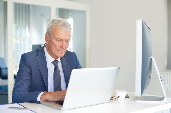 Older man in suit at a laptop.