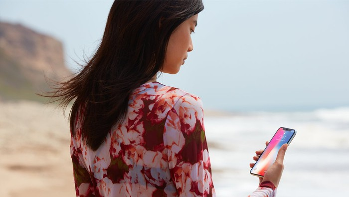 A woman walking on a beach looking at an iPhone X.