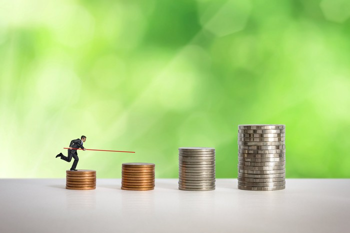 A pole-vaulting toy figurine preparing to vault across a series of stacked coins against a green background