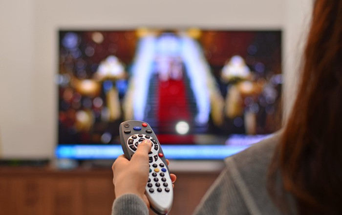 A woman pointing a remote control device at a TV in the background.