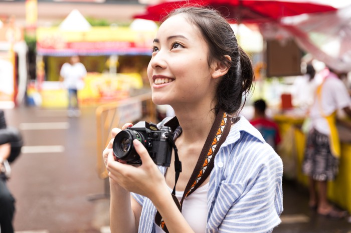 A Chinese woman holds a camera around her neck.