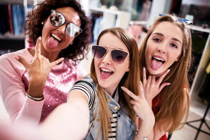 Three young girls taking a selfie while they shop.
