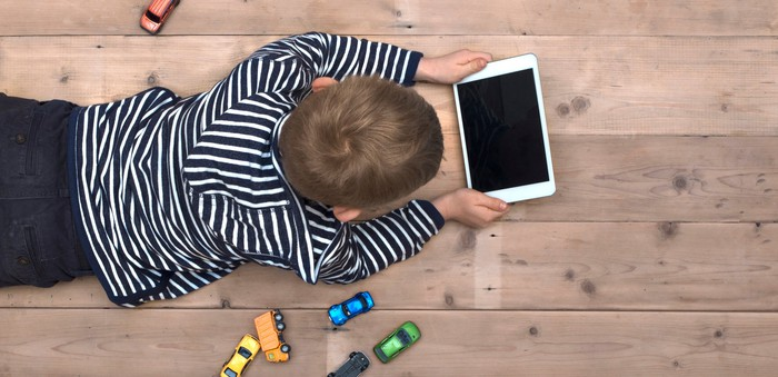 A young boy looks at a tablet computer while lying on the floor with toy cars scattered around him.