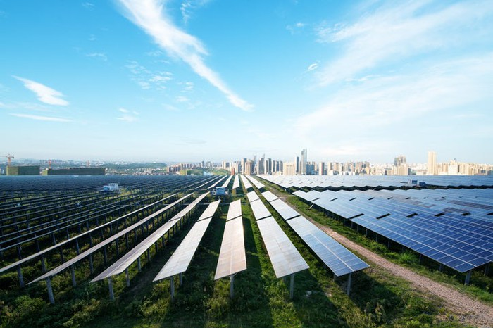 A utility-scale solar array on the outskirts of a city.