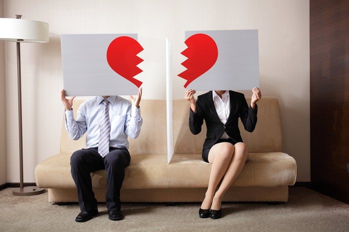 A man and a woman each hold half a torn paper heart.