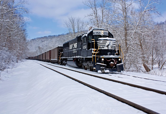 A Norfolk Southern engine navigating through a snowy landscape.