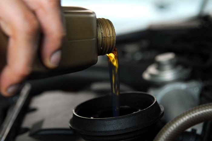 A hand pouring motor oil into a car engine.