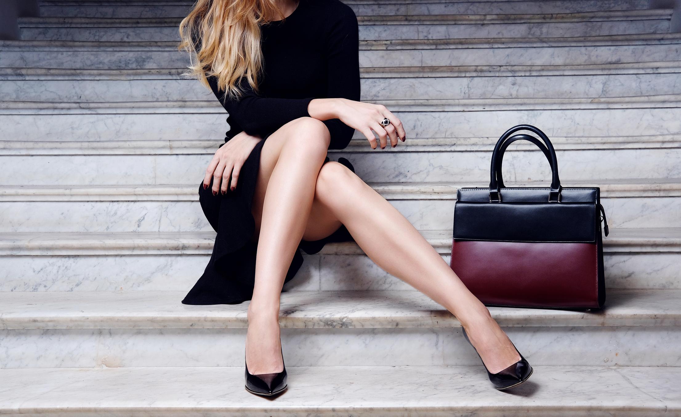 Woman sitting on steps next to luxury handbag.