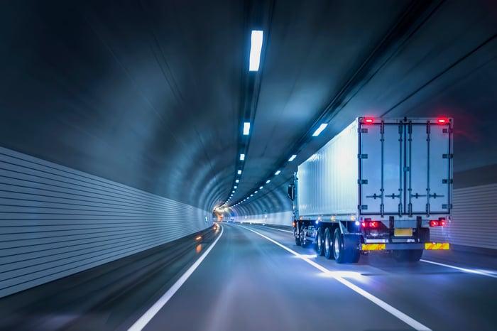 A freight truck passes through an illuminated tunnel.
