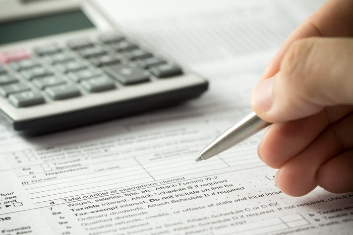 A tax form with a calculator and a hand with a pen above it.
