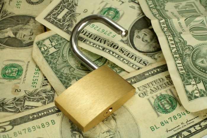 An open padlock sits on top of a scattered pile of U.S. currency.