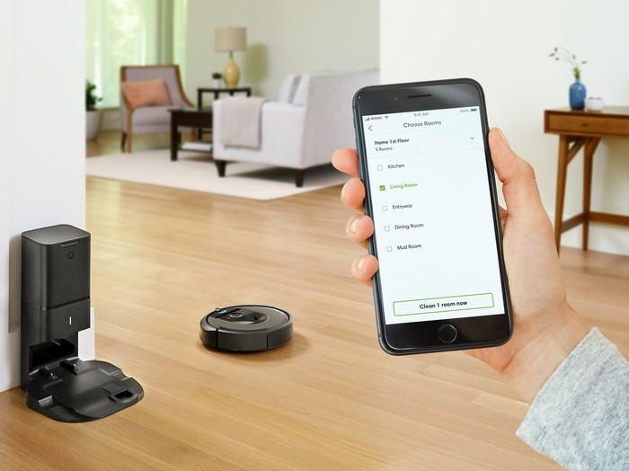 Hand with iRobot HOME app open and Roomba i7+ with cleaning base in the background.