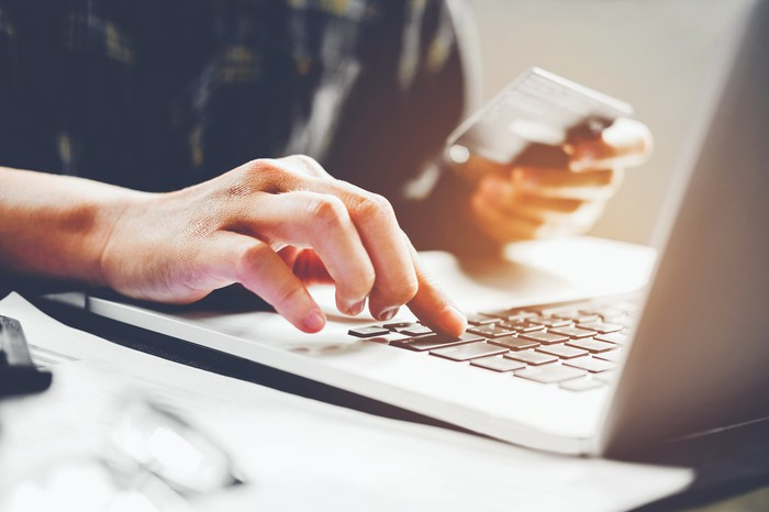 A man uses his credit card to make a purchase on a laptop.
