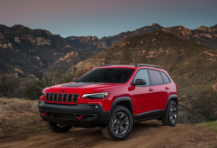 A red 2019 Jeep Cherokee Trailhawk, a midsize SUV, on a mountain trail