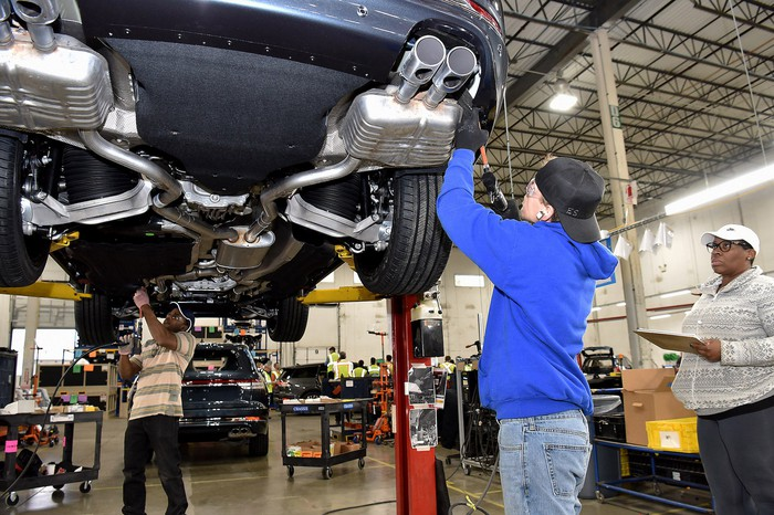 Two workers are shown attaching parts to a 2020 Ford Explorer, a midsize crossover SUV, in a factory setting.