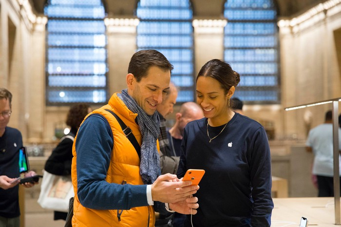 A customer holding an orange iPhone XR and an Apple employee looking at the phone.