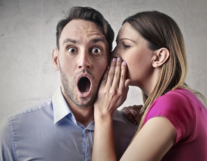 Woman whispering to a man whose mouth is wide open in surprise.